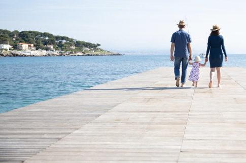 Un couple et leur fille marchent de dos sur un ponton de plage. Photo prise lors d'une séance grossesse par Myriam Ohayon Photographe à Antibes