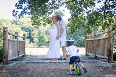 n couple pose pour une séance photo grossesse avec leur fils qui fait du vélo. Photo prise lors d'une séance grossesse par Myriam Ohayon Photographe à Nice