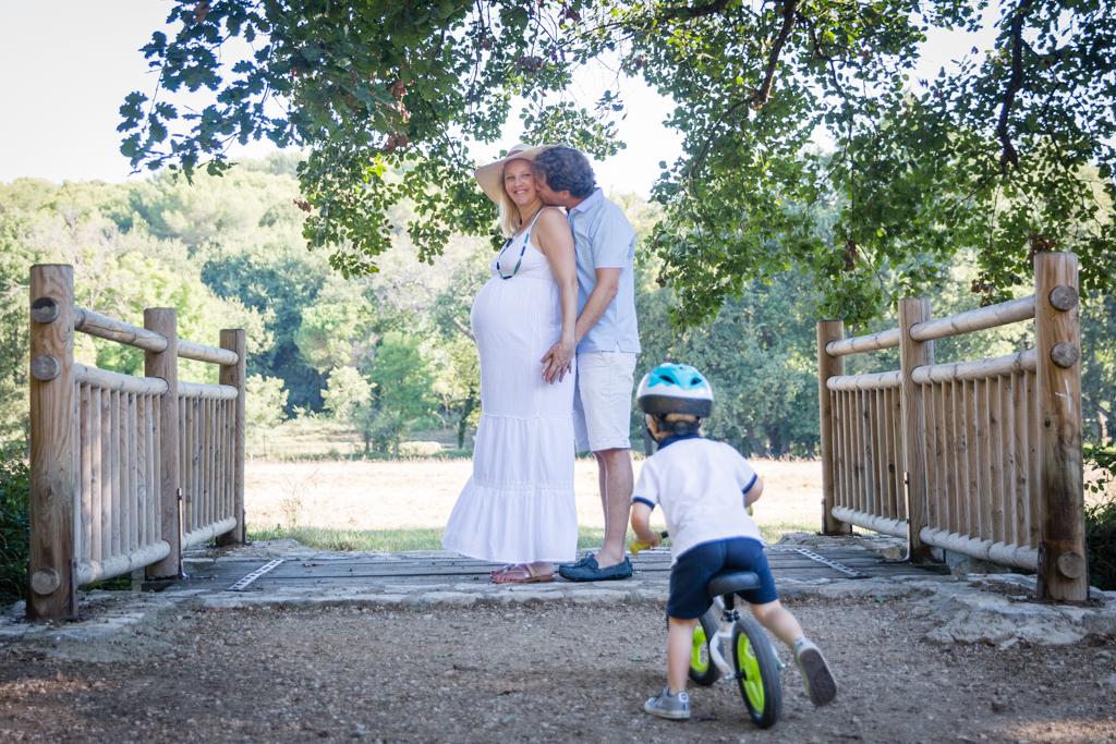 Une future maman enceinte et son mari posent dans un parc lors d'une séance photo grossesse. Photo prise par Myriam Ohayon Photographe à Nice.