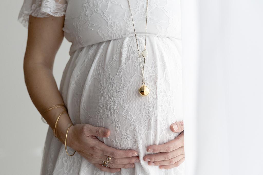 Gros plan sur un ventre de femme enceinte. Photo prise lors d'une séance grossesse à domicile à Nice. Myriam Ohayon Photographe