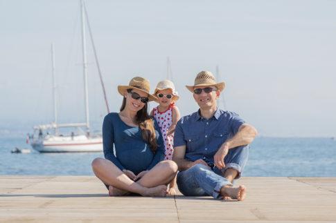 Un couple pose avec leur fille assis sur un ponton d plage à Antibes lors de leur séance photo grossesse. Photo prise par Myriam Ohayon Photographe