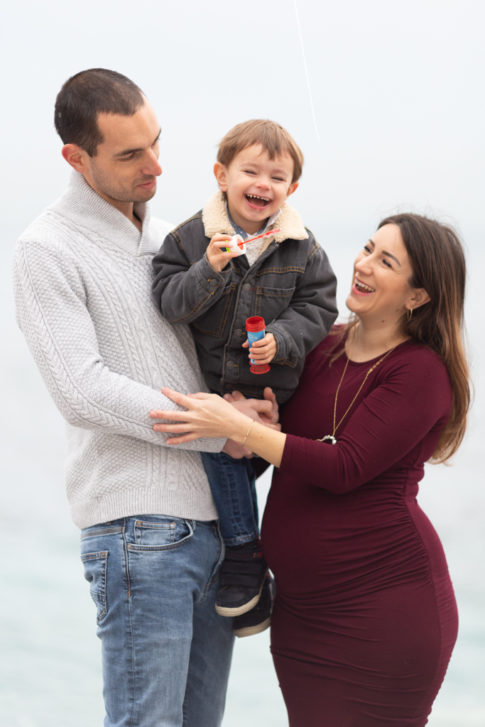 Photo d'une femme enceinte, son mari et leur fils riant aux éclats. Photo prise par Myriam Ohayon Photographe à Nice