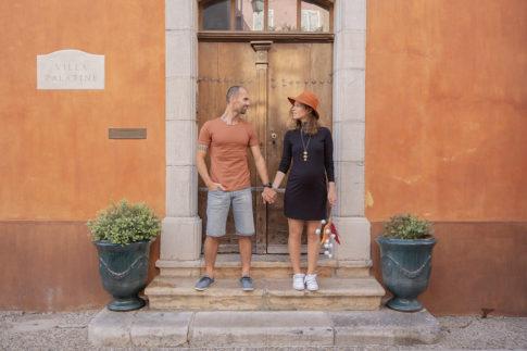 Un couple avec la femme enceinte pose devant une porte dans un village du var