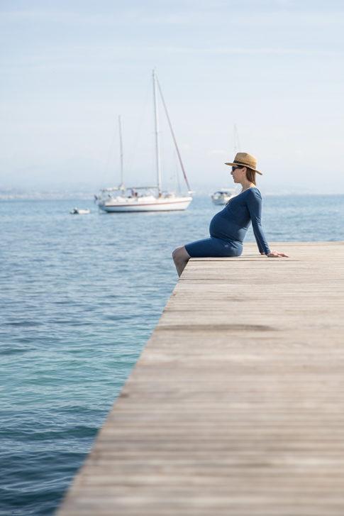 femme enceinte assise sur un ponton à Antibes. Photo prise par Myriam Ohayon Photographe