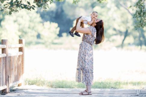 Une maman porte son fils de un an dans ses bras dans le parc de Vaugrenier à Nice. Séance photo en famille par Myriam Ohayon Photographe.