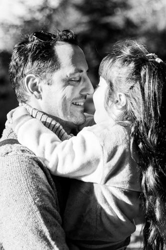 Un papa fait un câlin à sa fille lors d'une séance photo en famille à Cannes. Photo prise par Myriam Ohayon Photographe