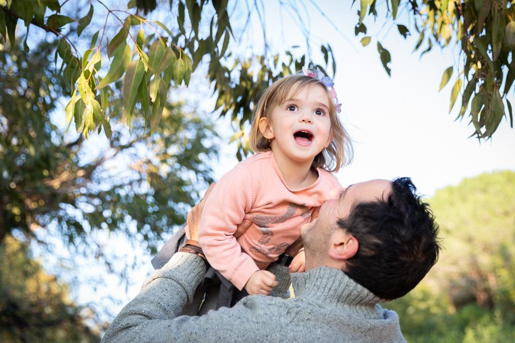 un papa s'amuse avec sa fille lors d'une séance photo en famille à Cannes. Photo prise par Myriam Ohayon Photographe