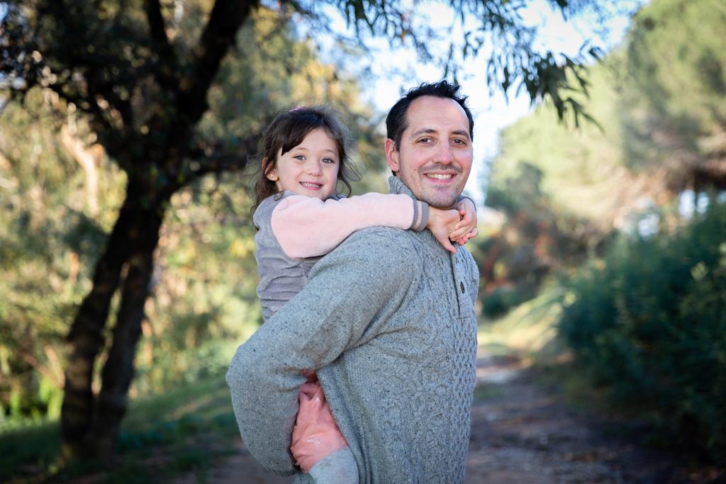 Une petite fille est sur le dos de son papa. Photo prise lors d'une séance photo en famille à Cannes. Myriam Ohayon Photographe