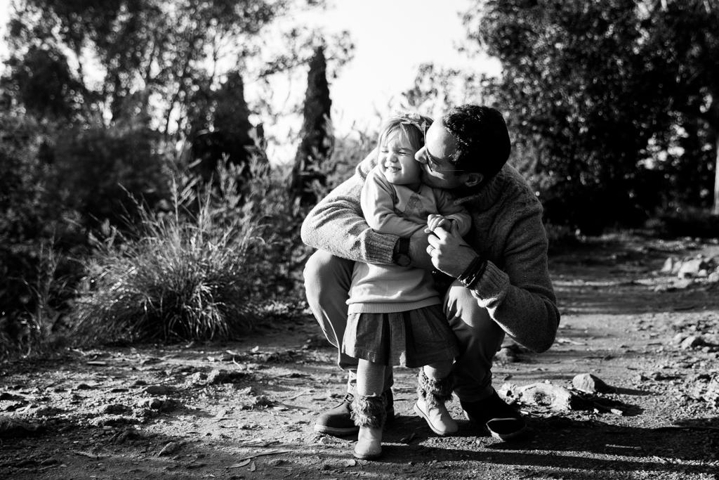 Un papa fait un câlin à sa fille lors d'une séance photo en famille à Cannes. Photo prise par Myriam Ohayon Photographe à Cannes