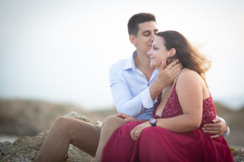 un homme embrasse sa femme sur le front. Séance d'engagement aux Issambres. Photo prise par Myriam Ohayon Photographe