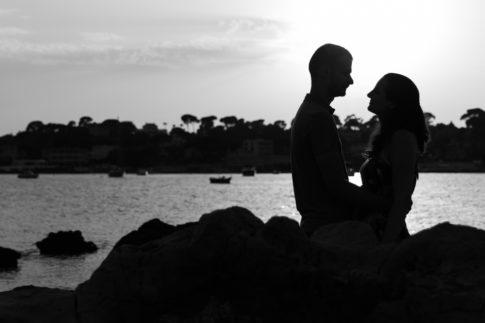 Photo de couple en silhouette sur les rochers du Cap d'Antibes. Séance d'engagement . Myriam Ohayon Photographe