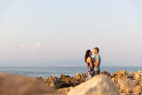 Photo de couple sur les rochers du Cap d'Antibes. Séance d'engagement . Myriam Ohayon Photographe