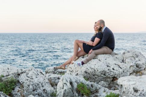 Photo d'un couple assis sur des rochers lors de leur séance d'engagement près de Monaco. Photo prise par Myriam Ohayon Photographe