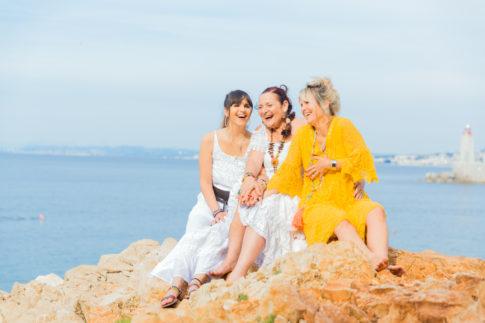 Une maman et ses deux filles sont assises sur des rochers d'une plage de Nice. Photo prise par Myriam Ohayon Photographe.