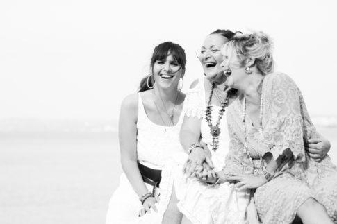 Une maman et ses deux filles sont assises sur des rochers d'une plage de Nice. Photo en noir et blanc prise par Myriam Ohayon Photographe.