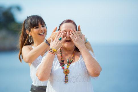 Une fille met ses mains sur les yeux de sa maman pour lui faire deviner qui elle est. Séance photo en famille à l'occasion de la fête des mères.
