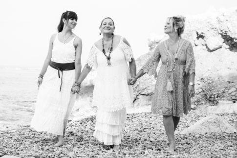 Une maman se promène avec ses deux filles sur une plage de galets à Nice lors d'une séance photo en famille. Photo en noir et blanc prise par Myriam Ohayon Photographe.