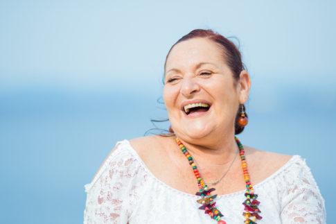 Gros plan sur un visage d'une femme qui éclate de rire lors d'une séance photo en famille à Nice.