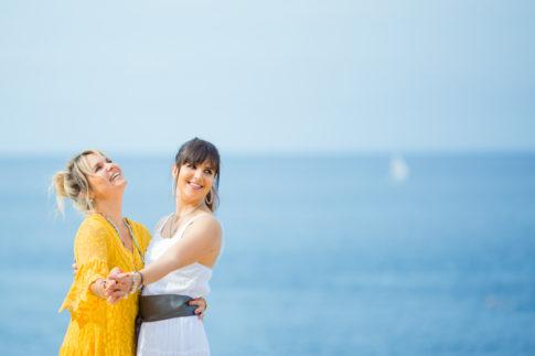 Deux soeurs dansent sur la plage, la mer est en fond. Photo prise lors d'une séance photo Fête des mères à Nice.