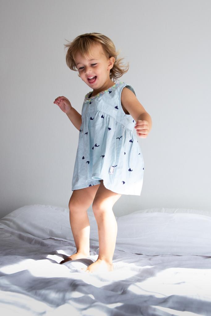 une petite fille saute sur un lit pendant une séance photo naissance. Myriam Ohayon Photographe