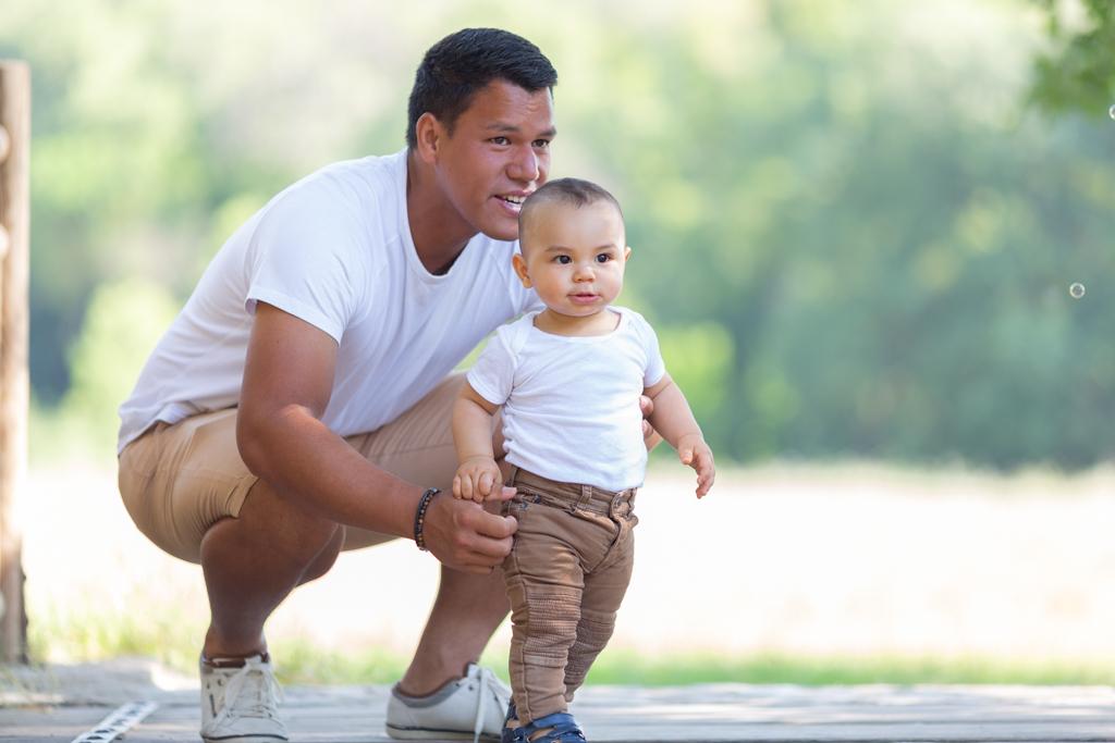 Un garçon d'un an pose avec son papa lors d'une séance photos en famille.