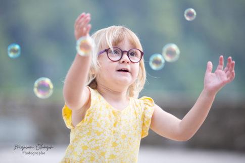 Séance photo en famille à Eze . Portrait d'une petite fille qui joue avec des bulles par Myriam Ohayon Photographe