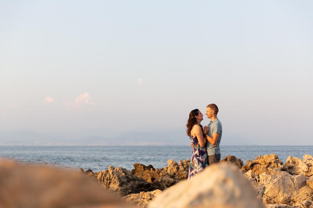 Un couple pose face à face pendants a séance d'engagement à Antibes près de la mer