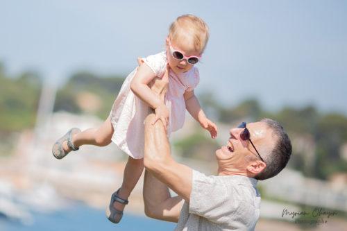 Un papa joue avec sa fille sur la plage d'Antibes.