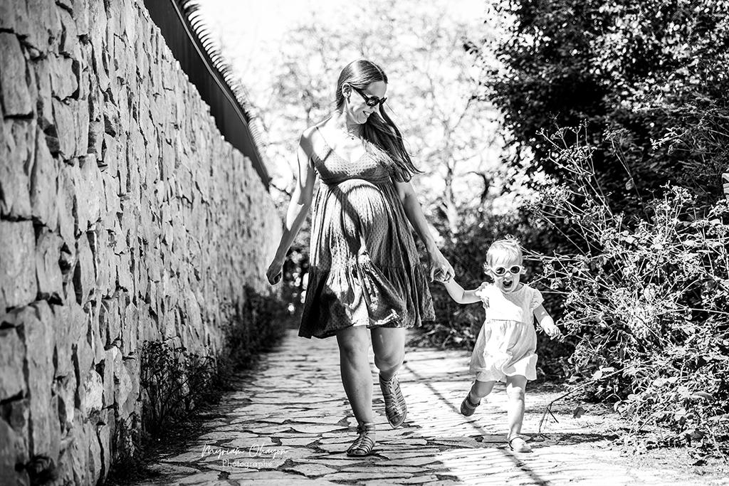 Une femme enceinte se promène avec sa fille sur le sentier du littoral à Antibes lors de sa séance photo grossesse.