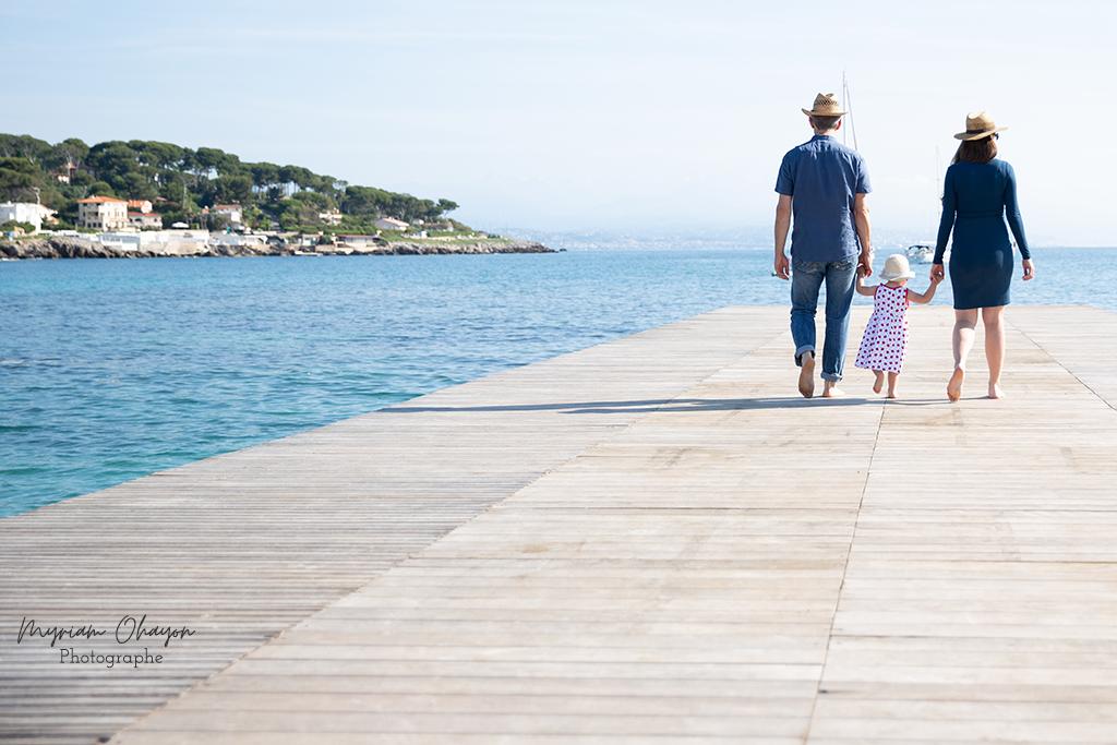 Un papa, une maman et sa fille posent marchent de dos sur un ponton de la plage d'Antibes.