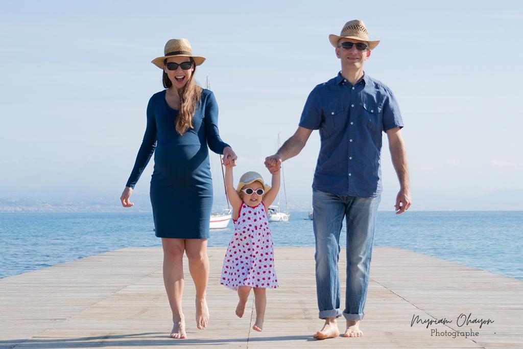 une femme enceinte et son mari pose sur la plage avec leur première fille.