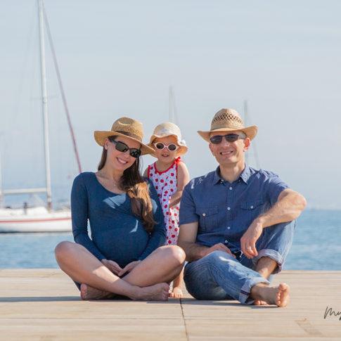 Un couple avec la femme enceinte pose avec leur fille aînée assis sur un ponton de plage à Antibes. Photo prise par Myriam Ohayon Photographe