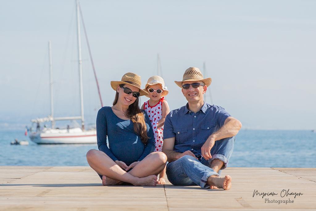 une femme enceinte, son mari et leur fille assis sur le ponton de l plage d'Antibes à l'occasion d'une séance photo grossesse en famille.