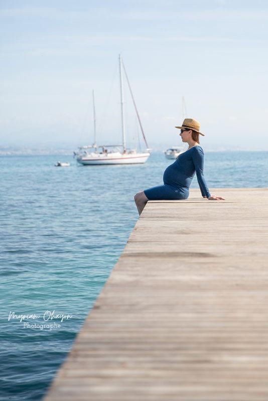 Une femme enceinte est assise sur un piton face à la mer.