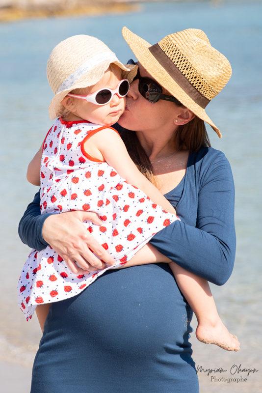 Une femme enceinte embrasse sa fille aînée qu'elle tient dans ses bras.