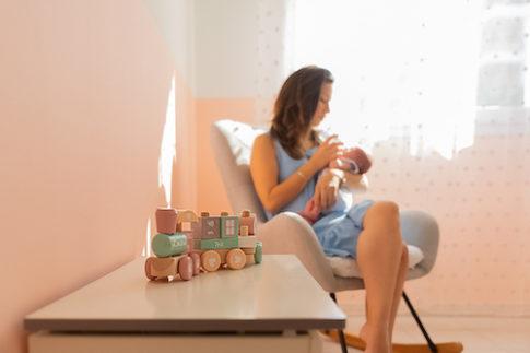Une maman donne le biberon à son bébé pendant leur séance photo naissance à domicile à Nice.