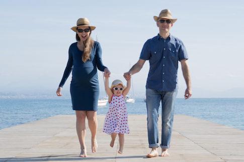 Un papa, une maman enceinte et leur petite fille marchent sur un ponton de plage à Antibes.