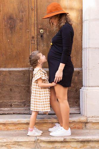 Portrait d'une petite fille de 4 ans et de sa maman enceinte.