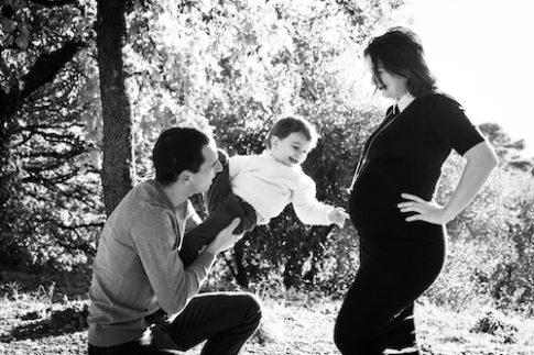 Un petit garçon montre le gros ventre de sa maman enceinte. Photo en noir et blanc.