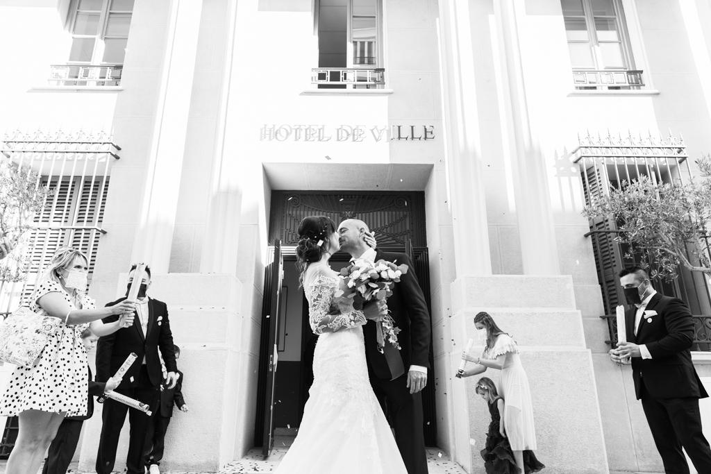 Photo en noir et blanc d'un couple qui s'embrasse à la sortie de la mairie de Nice. Photo prise par Myriam Ohayon Photographe à Nice