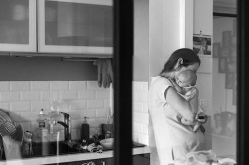 Une maman porte son bébé dans ses bras. Photo en noir et blanc prise lors d'une séance naissance à domicile à Antibes.
