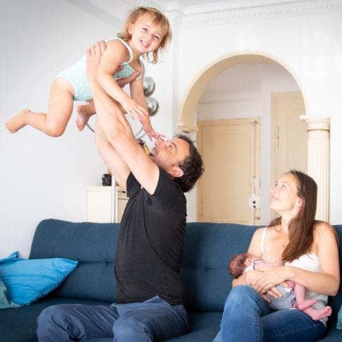 Un papa joue avec sa fille pendant que la maman allaite leur bébé. Photo prise lors d'une séance photo naissance à Nice.Photo prise par Myriam Ohayon Photographe