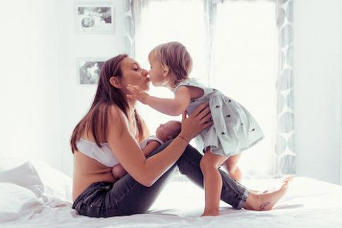 Une maman embrasse sa fille sur son lit. Photo prise lors d'une séance naissance à domicile à Nice.