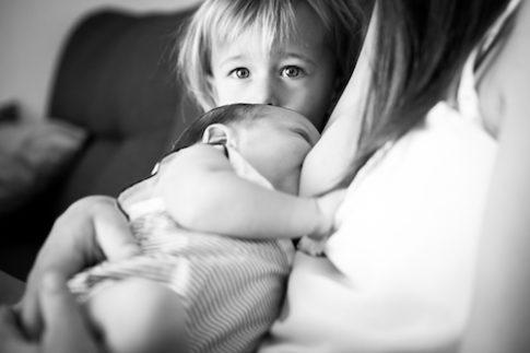 Une petite fille regarde sa maman qui allaite son frère. Photo prise lors d'un reportage naissance à domicile à Nice.