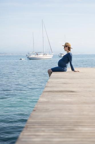 Une femme enceinte pose assise lors d'une séance photo grossesse à Antibes.
