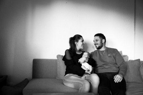 Photo d'un couple et son bébé sur leur canapé. Photo prise lors d'un reportage naissance à domicile par Myriam Ohayon Photographe.