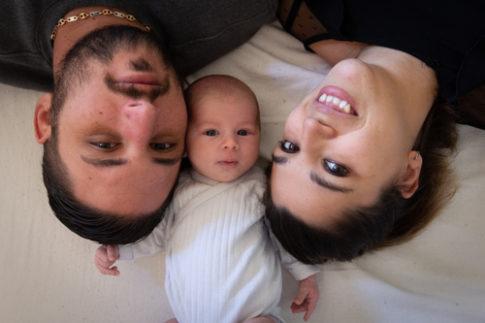 Gros plan sur le visage d'un papa, d'une maman et de leur bébé.