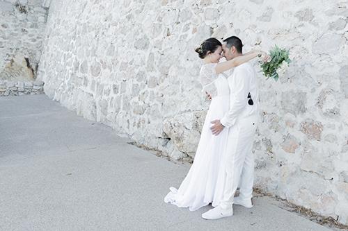 Un couple de mariés pose pour leurs photos de couple près d'un mur de pierres. Photo prise par Myriam Ohayon Photographe