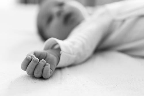 Photo en noir et blanc d'un gros plan sur la main d'un nourrisson. Photo prise par Myriam Ohayon Photographe