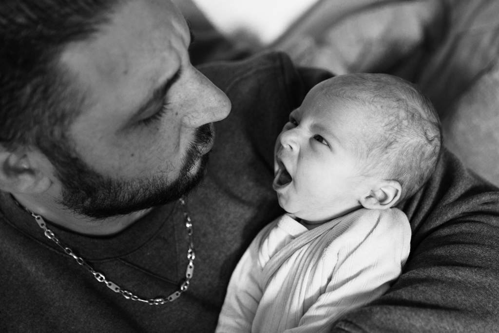Photo en noir et blanc d'un bébé qui baille devant son papa. Photo prise par Myriam Ohayon Photographe lors d'une séance photo naissance à Nice